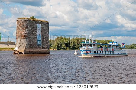 VELIKY NOVGOROD, RUSSIA - JULY 17, 2012: Tourist boat sails near pillar on The Volkhov River not far from Riurik's fortress and Veliky Novgorod