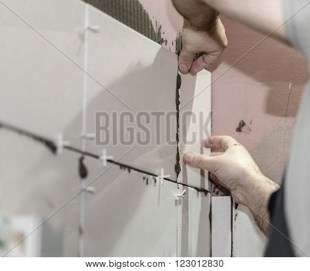 Worker tiler puts ceramic tiles on a wall
