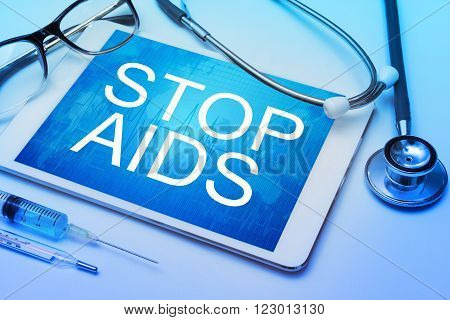 Stop AIDS word on tablet screen with medical equipment on background