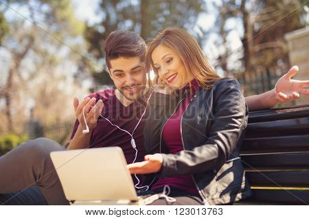 Young couple with laptop sitting on bench outdoor websurfing on internet