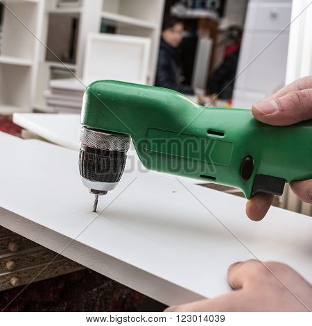 Carpenter Drills A Hole In The Component Parts Of A White Kitchen Cabinet For Fastening Pins Wall Ca