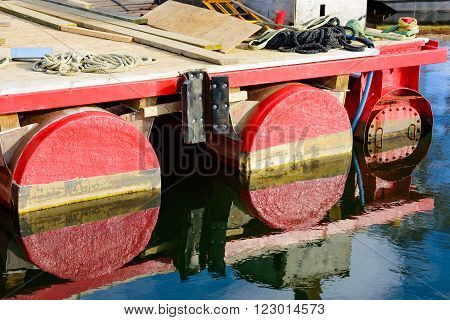 Detail of the side of a floating work platform at sea. Rope tools and debris lie on the platform. Water is still on this sunny day so there are fine reflections of the red floating devices.