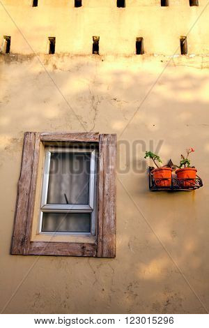A rustic wooden window frame with a juxtaposing modern window.