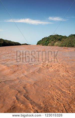 A muddy river bursts it's banks in St Lucia
