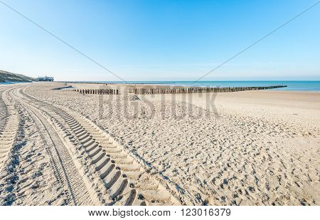 A long meandering trail of the tire imprints of a tractor in the sand of the North Sea beach on a sunny day in winter time.