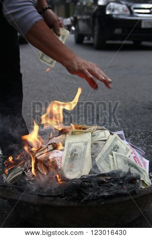 Money burning. Person burns fake US Dollars and Vietnam Dongs on the street in Hanoi becouse needn't them any more.