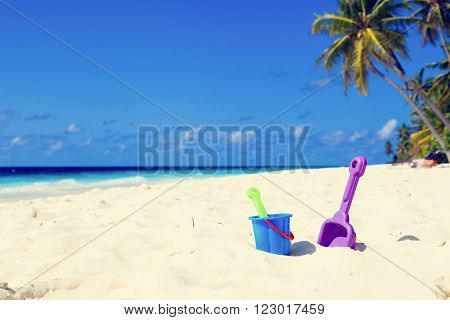 kids toys on tropical sand beach, family vacation