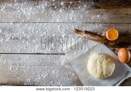 Prepared dough . The dough and ingridient for him . On the wooden table. Top view