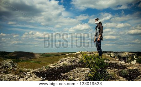 Wide image of man vaping electonic cigarette and staying on rocky hills against blue cloudy sky. With vignette.