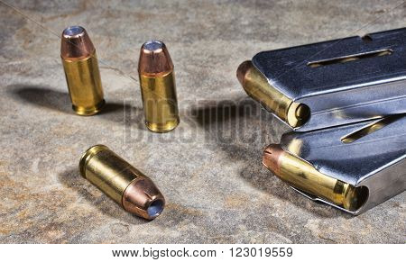 Cartridges with hollow point bullets for a handgun with magazines