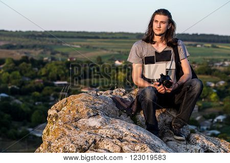 Handsome young longhair man sitting on a rocks with digital dslr camera against fields and blue background. Sunset shot.