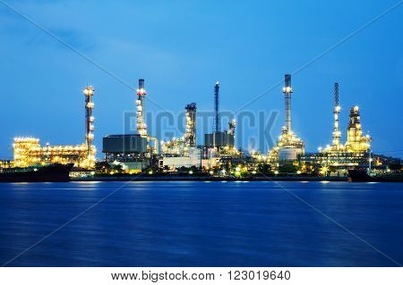 Oil refinery industry with tube and oil tank along twilight sky