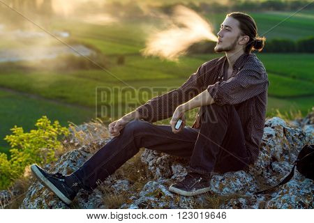 Handsome young man sitting on a rocks and smoking electronic cigarette at outdoors. ** Note: Soft Focus at 100%, best at smaller sizes