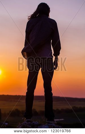 Silhouette of young longhair male model at red and purple sunset.