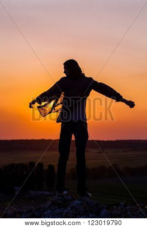 Silhouette of young longhair male model with opened hands at red and purple sunset sky.