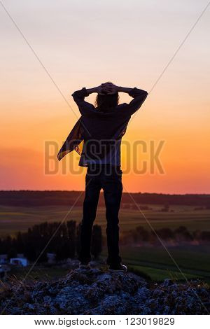 Silhouette of young longhair male model with heads over head against red and purple sunset sky.