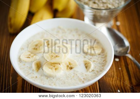 boiled sweet porridge with a banana on the table