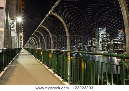 BRISBANE, AUSTRALIA - MARCH 3 2016: Brisbane Story Bridge walkway and suicide mesh wall prevention barriers, over looking Brisbane cityscape by night.
