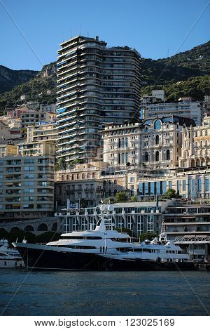 Monte Carlo, Monaco - September 20, 2015: yachts black and white modern vessels at moorage in sea port on sunny summer day against mountains on cityscape background, vertical picture