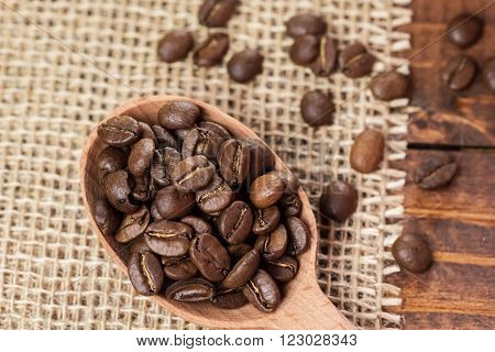 Whole Coffee Beans In A Wooden Spoon And A Scattering Of Coffee Beans On Burlap And Old Brown Boards