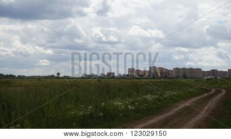 city outskirts. Photo of a green summer meadow on the background of brick town houses