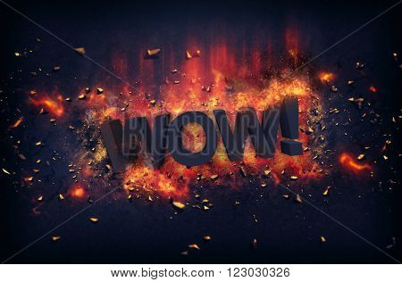 Burning orange fiery flames and explosive sparks on a dark background with the word - WOW ! - in black text for a dramatic poster design