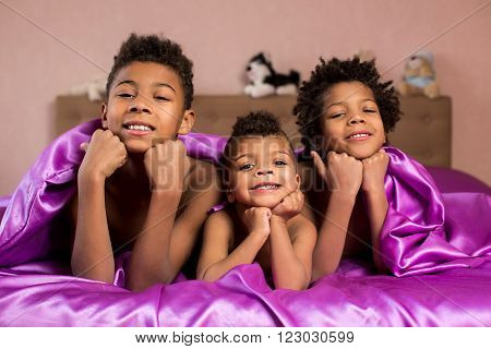 Mulatto kids smiling widely. Three happy children on bed. Happiness as it is. Purity of true emotions.