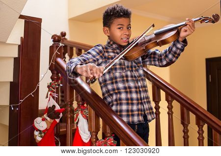 Smiling afro kid plays violin. Boy playing violin on Christmas. Young violinist's smile. True Christmas concert.