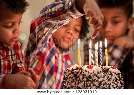 Boy holding finger over candle. Kid playing with cake's candles. Don't burn yourself. Old enough to try this.