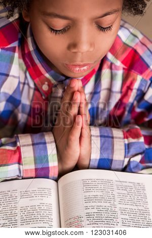 Mulatto boy praying. Kid in shirt is praying. Young man with prayer-book. His faith is strong.