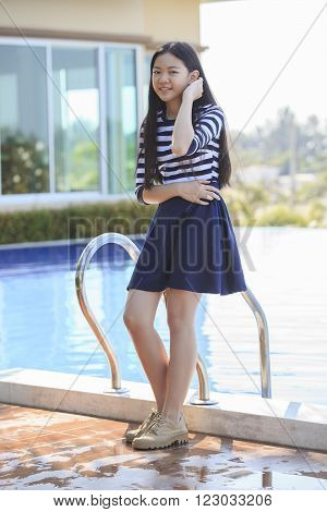 portrait of asian teen age smilling face standing in home swimming pool with relax and happy emotion