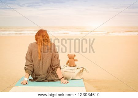 Young single woman sitting at beach with teddy bear looking at the sea - Solitude and loneliness concept with imaginary friendship and melancholic feelings - Warm vintage filter with enhanced sunshine