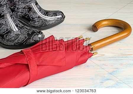 Umbrella and rubber boots on a light wooden background.