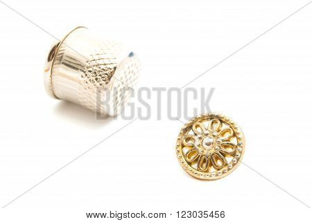 Plastic Button And Thimble On White