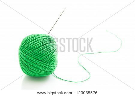 Spool Of Green Thread And Needle On White