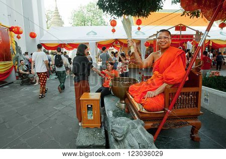 BANGKOK, THAILAND - FEB 14: Monk sprinkles holy water temple visitors inside famous monastery Wat Pho on February 14, 2015. Wat Pho is a Buddhist temple complex founded in 16th century