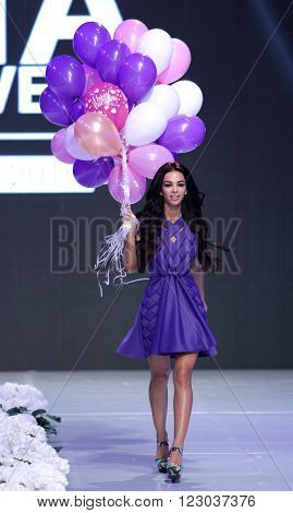 Sofia Bulgaria - March 23 2016: A model walks the runway with balloons at Sofia Fashion Week runway show. The fashion show is held for a second time in Bulgaria's capital.