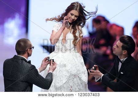 Sofia Bulgaria - March 23 2016: Two male models are proposing a marriage at the runway to a female model at Sofia Fashion Week runway show. The fashion show is held for a second time in Bulgaria's capital.