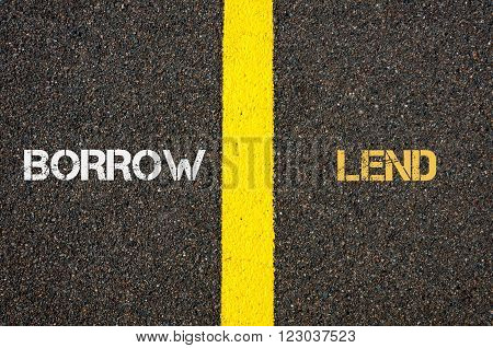 Antonym concept of BORROW versus LEND written over tarmac, road marking yellow paint separating line between words