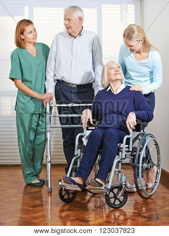 Woman doing elderly care with senior couple at home