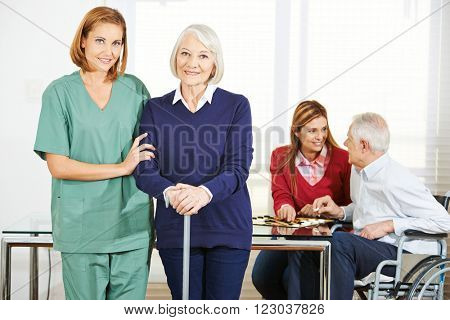 Caregiver working with happy senior people in nursing home