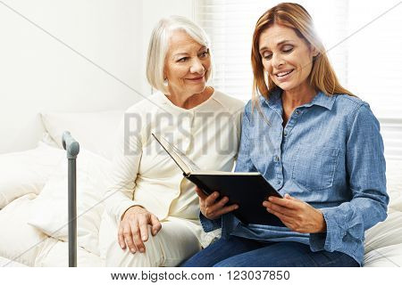 Old woman and daughter looking at photo album together at home