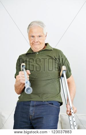 Senior man fighting with crutches at home