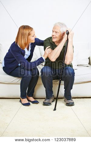 Caregiver talking to senior man at home on a sofa