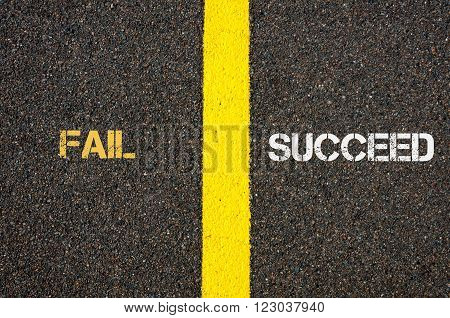 Antonym concept of FAIL versus SUCCEED written over tarmac, road marking yellow paint separating line between words
