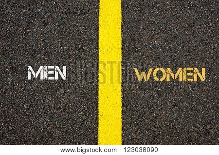 Antonym concept of MEN versus WOMEN written over tarmac, road marking yellow paint separating line between words