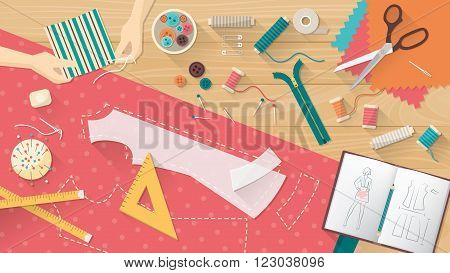 Tailor working and sewing a shirt sewing equipment patterns and sketchbook on the work table dressmaking concept