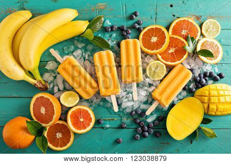 Mango banana popsicles on ice with fresh fruits and berries