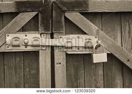 Padlock and a locking bar on an old wooden door (in sepia vintage style)