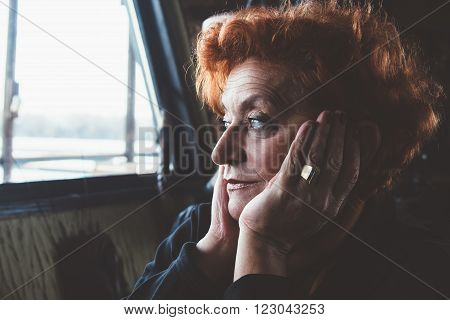 Worried mature woman looking through the window